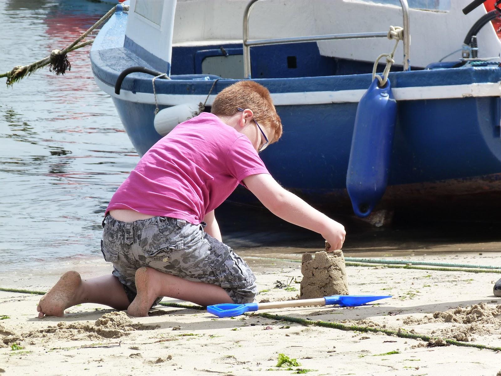 Boy builds sandcastle